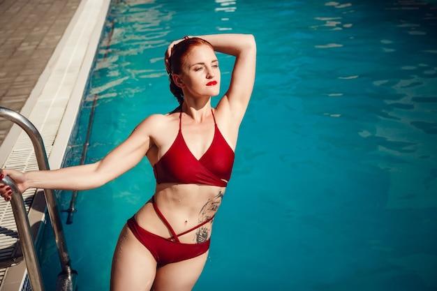 Buntes porträt der hübschen jungen frau im roten badeanzug, der nahe schwimmbad liegt