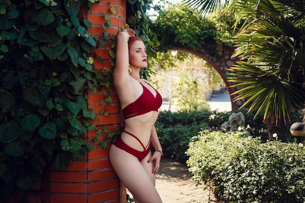 Buntes porträt der hübschen jungen frau im roten badeanzug