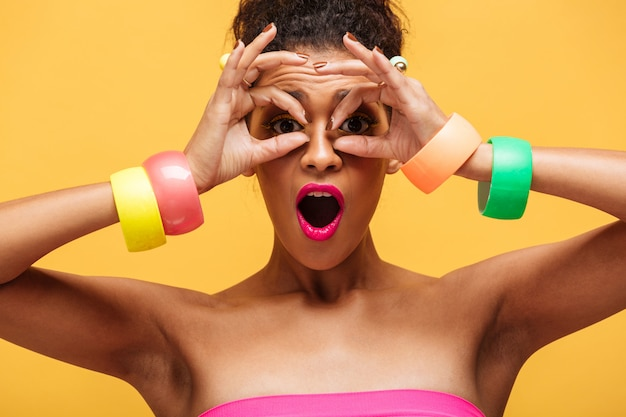Buntes porträt der reizenden mischrassefrau mit modemake-up und -schmuck auf den händen, die kamera durch die finger lokalisiert, über gelber wand betrachten