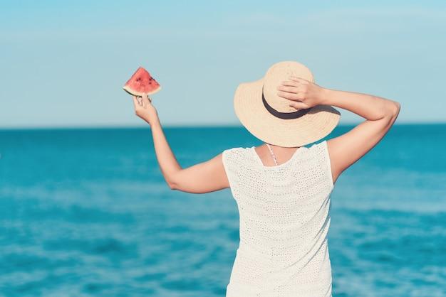Buntes porträt des mädchens wassermelone auf einem schönen tropischen strand halten.
