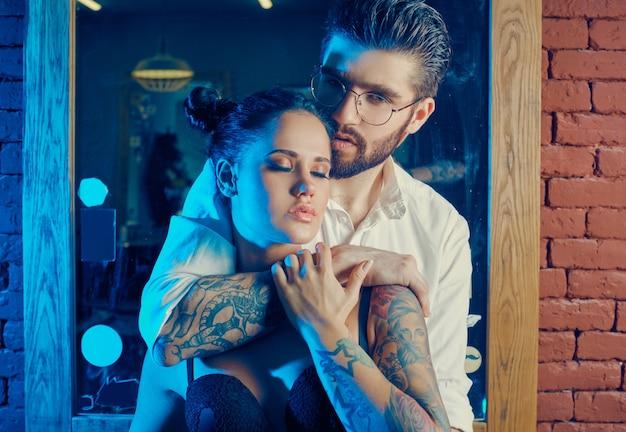 Buntes porträt des schönen paares: brutaler mann im eleganten anzug und mädchen mit einem tattoo, das dessous im friseursalon trägt
