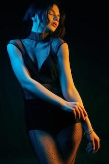 Buntes porträt einer sinnlichen schönen brünetten frau in einem sexy modekleid, das auf einem schwarzen im studio aufwirft