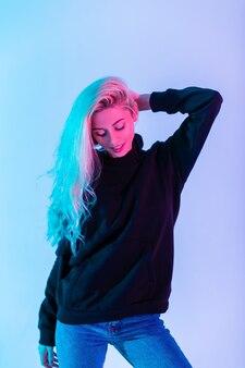 Buntes porträt eines jungen schönen mädchens mit blonden haaren in einem schwarzen modischen hoodie mit blue jeans auf neonrosa hintergrund