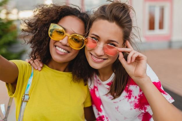 Buntes porträt von glücklichen jungen mädchenfreunden, die lächelnd sitzen auf der straße selfie-foto auf handy, frauen, die spaß zusammen haben