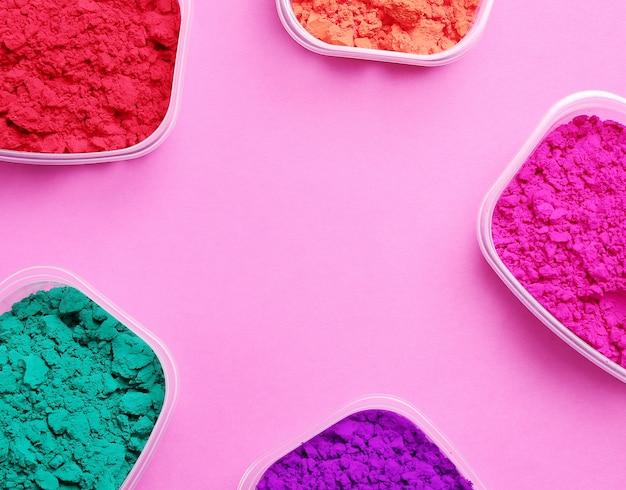 Buntes pulver auf rosa hintergrund, holi festival-konzept