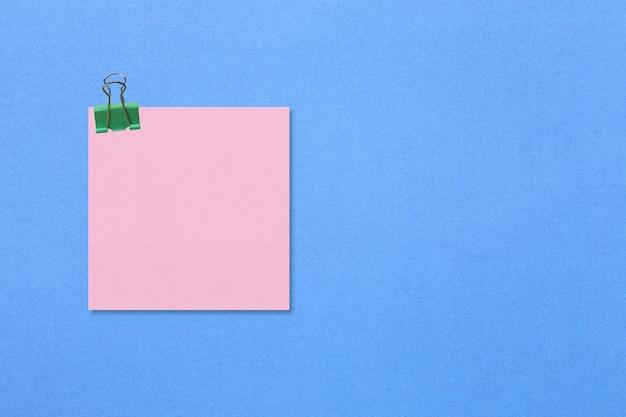 Buntes quadratisches notizpapier auf blauem papier