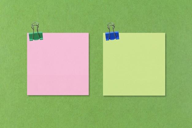 Buntes quadratisches notizpapier auf grünem papier