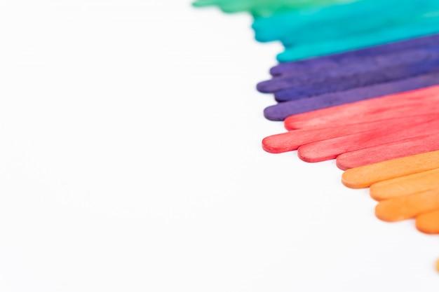 Buntes regenbogenholz-eis am stiel auf weißem papier