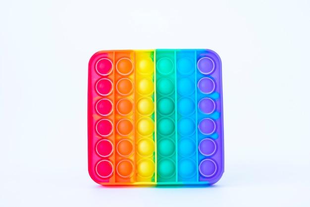 Buntes regenbogenpoppit-spiel. silikon zappeln nahaufnahme auf weißem hintergrund.