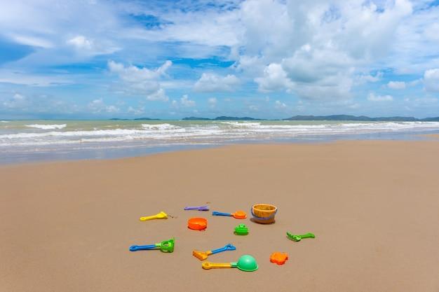 Buntes sandspielzeug auf dem weißen sandstrand zur sommerzeit.