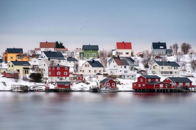 Buntes skandinavisches holzhaus auf schneebedecktem an der küstenlinie