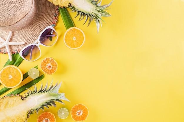 Buntes sommer- und feiertagskonzept, strohhut, sonnenbrille, palmzweige, ananas und sternfisch gelber hintergrund.