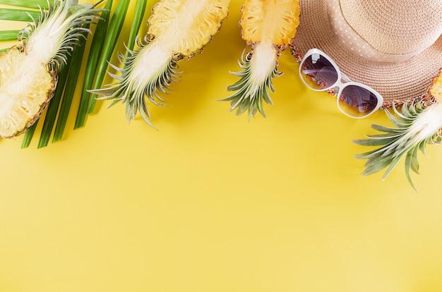 Buntes sommer- und feiertagskonzept, strohhut, sonnenbrille, palmzweige und ananas auf gelbem hintergrund.