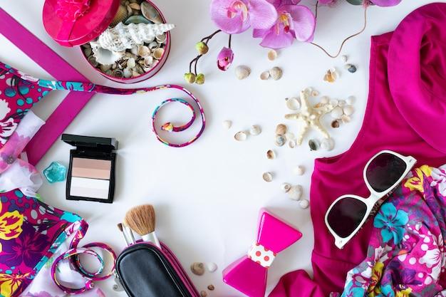 Buntes sommerfrauenmode flaches outfit. kleid, sonnenbrille, kosmetik, parfüm, blumen auf weißem hintergrund, draufsicht, breite komposition. sommermode, urlaubskonzept