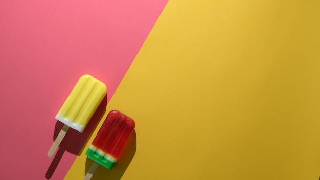 Buntes sommerkonzept mit eis am stiel mit wassermelone und zitronengeschmack