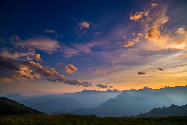 Buntes sonnenlicht auf den majestätischen berggipfeln, grünen weiden und nebligen tälern der italienischen alpen. goldenes wolkengebilde bei sonnenuntergang.