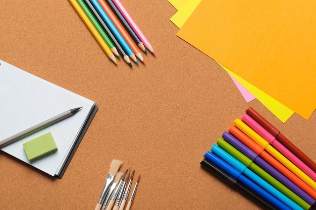 Buntes sortiment an filzstiften und papierbögen für die kreation
