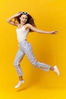 Buntes studiobild der trendigen modischen jungen frau mit losem haar und schlankem körper
