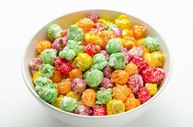 Buntes süßes popcorn von einem shop in der weißen schüssel. leckerbissen.