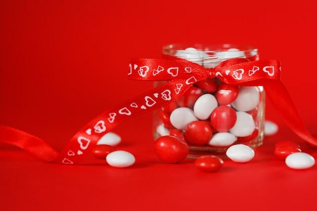 Buntes süßigkeitsglas verziert mit herzen eines rotbogens. valentinstag-konzept