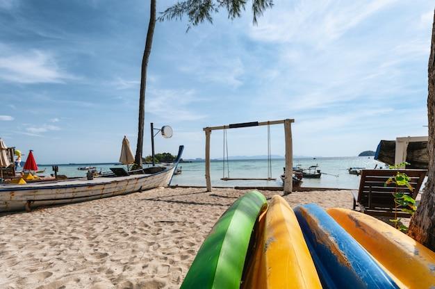 Buntes surfbrett mit hölzernem schwingen auf dem strand im tropischen meer