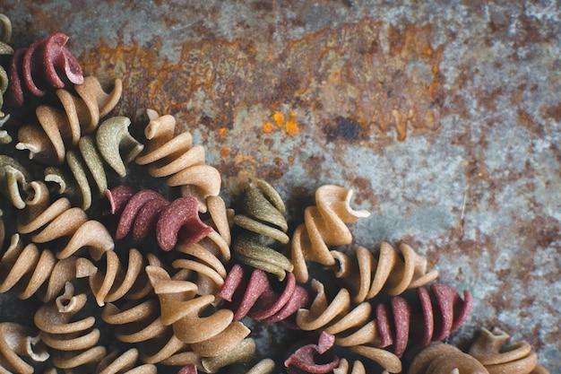 Buntes teigwaren fusili detail über einen rostigen metallischen hintergrund
