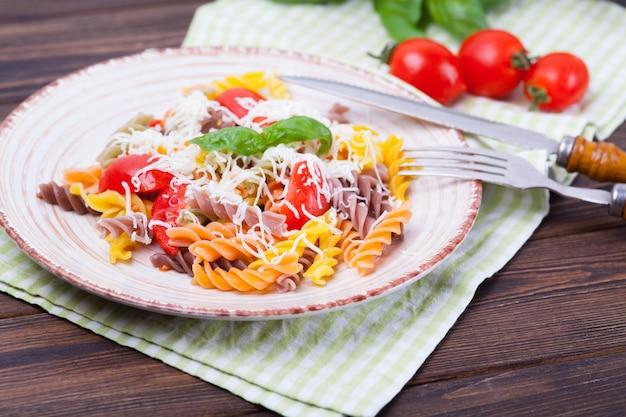 Buntes teigwaren fusilli mit tomate, basilikum und käse auf einem dunklen holztisch