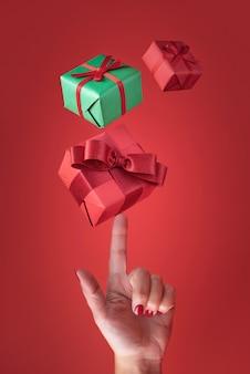 Buntes weihnachtsgeschenkpapier, das auf einer weiblichen hand auf einem roten hintergrund fliegt