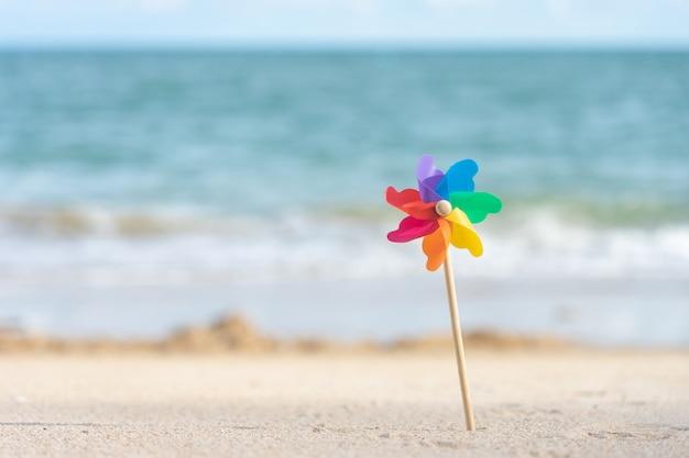 Buntes windmühlenpapier tagsüber gestickt auf dem strand seeansicht