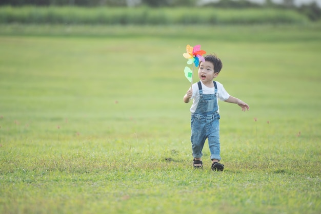 Buntes windmühlenspielzeug für kinder. lachendes kind, das glücklich spielt. kleiner junge bläst im sommer im sommerlager in der sonne gegen eine bunte windmühle.