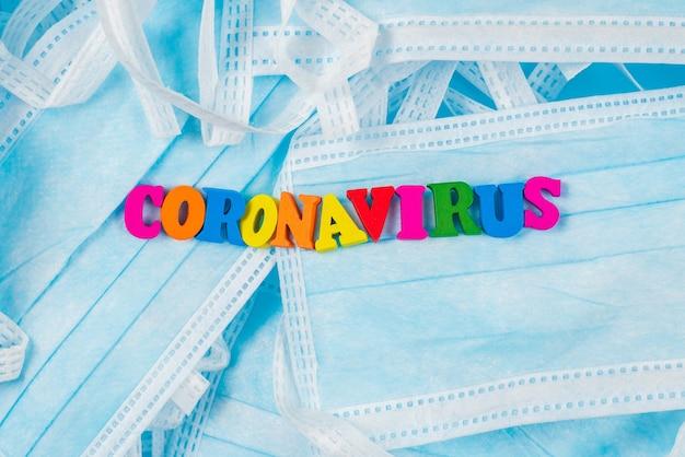 Buntes wort coronavirus auf schutzmasken. draufsicht.