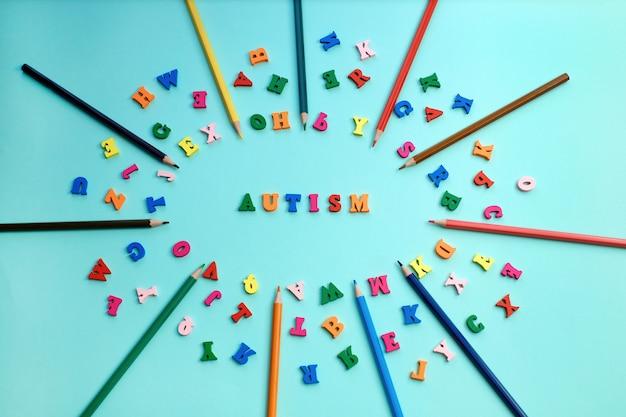 Buntes wort des autismus von farbigen hölzernen buchstaben und von farbbleistiften.