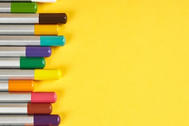 Buntstift auf hellgelbem hintergrund. sicht von oben. linker rand. stifte mit grauem körper und farbigen spitzen. leuchtende farben