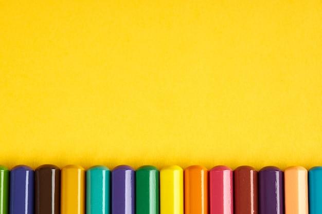 Buntstift auf hellgelbem hintergrund. sicht von oben. untere grenze. stifte mit grauem körper und farbigen spitzen. leuchtende farben