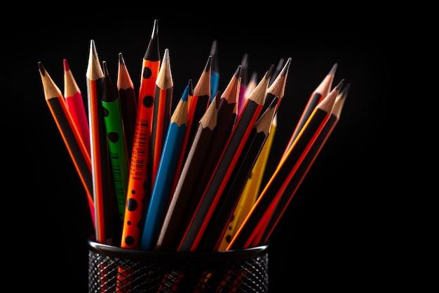 Buntstifte aus graphit zum zeichnen und schreiben in einem schwarzen kleinen korb auf einem schwarzen schreibtisch