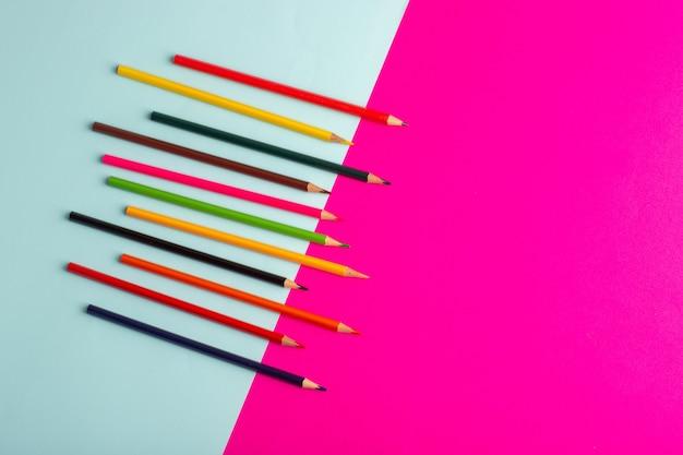 Buntstifte der draufsicht, die auf blauer und rosa schreibtischfarbzeichnungskunstfarbe gezeichnet werden