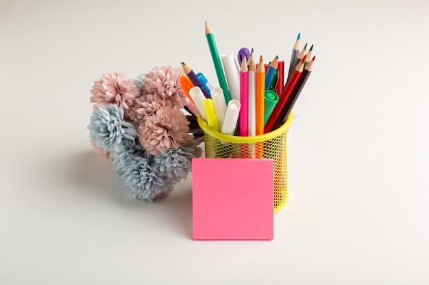 Buntstifte der vorderansicht mit blumen auf weißem schreibtisch