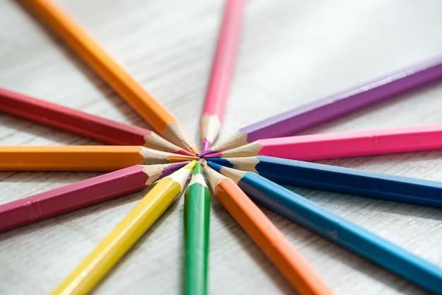 Buntstifte im kreis auf holzuntergrund angeordnet