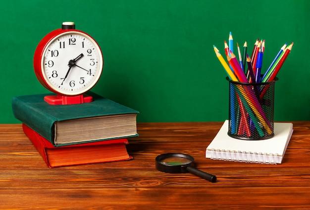 Buntstifte in einem ständer, ein notizbuch, ein wecker, bücher, eine lupe auf einem holztisch mit grünem hintergrund.