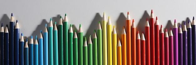 Buntstifte in verschiedenen farbtönen liegen in reihe auf weißem hintergrund