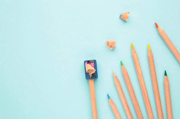 Buntstifte und anspitzer auf der blauen pastelloberfläche