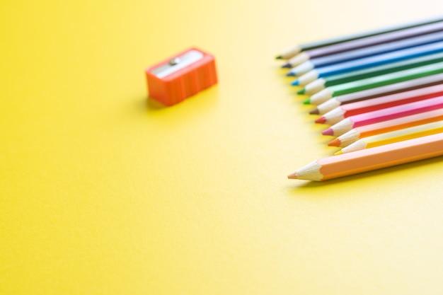 Buntstifte und bleistiftspäne auf dem gelben papierhintergrund.