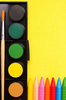 Buntstifte und farben auf gelbem papier. das konzept der kreativität und des zeichenunterrichts für kinder.