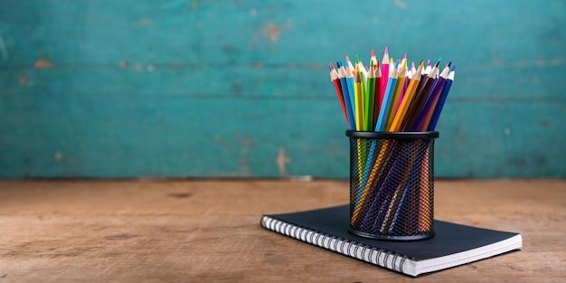 Buntstifte und notizbuch auf dem schreibtisch