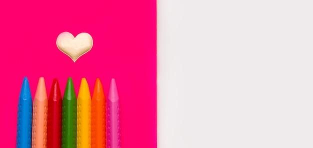 Buntstifte zum zeichnen verschiedener farben auf einem rosa notizbuch.