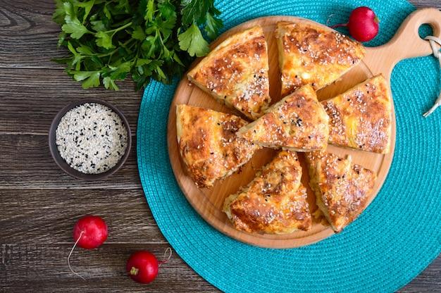 Burek türkische torte. lavash puff pie mit käse und sesam. draufsicht.