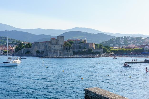 Burg in einem mittelalterlichen hafen mit booten und menschen am strand. reisekonzept