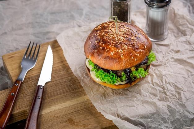 Burger auf dem holztisch mit messer und gabel. burger mit lamm