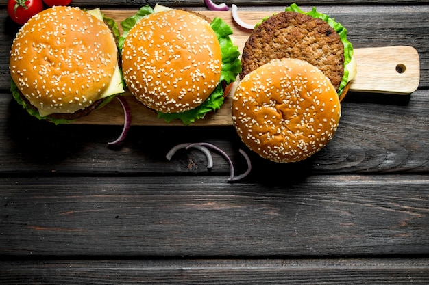 Burger auf einem hölzernen schneidebrett mit zwiebelscheiben auf rustikalem tisch