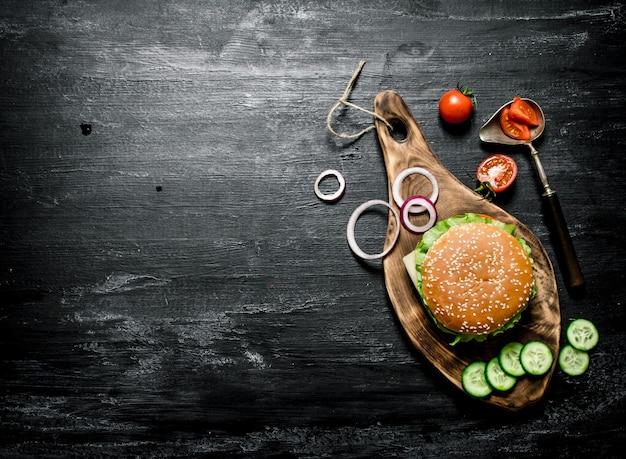 Burger auf einem schneidebrett mit gurke und kräutern. auf einer schwarzen tafel. draufsicht.